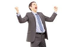 打手势兴奋用被举的手的年轻商人 免版税库存图片