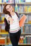 打手势thumbsup的大学生在图书馆里 免版税图库摄影
