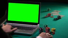 打扑克在网上在膝上型计算机的人,打赌在赌博的站点,绿色屏幕 股票视频