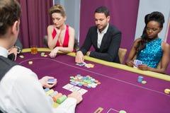 打扑克的男人和两名妇女 免版税库存照片