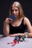 打扑克的美丽的白肤金发的妇女在暗室 库存图片