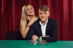 打扑克的年轻夫妇在赌博娱乐场 免版税库存照片