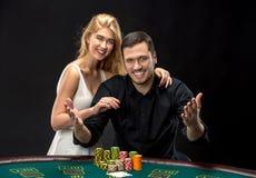 打扑克的年轻夫妇有好时光在赌博娱乐场 免版税图库摄影