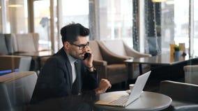 打打电话的严肃的商人使用在咖啡馆的智能手机 影视素材