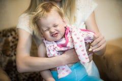 打扮她的小女婴的妈妈 库存图片