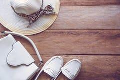 打扮妇女、袋子、鞋子和帽子的白色口气在木floo 库存照片