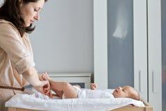 打扮婴孩的母亲 免版税图库摄影