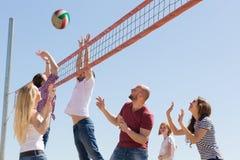 打排球的朋友在海滩 免版税图库摄影