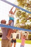 打排球的比赛家庭在庭院里 免版税库存照片