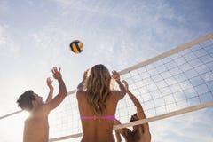 打排球的海滩朋友 免版税库存照片