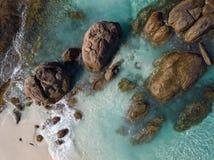 打旋在一个美丽的海滩的海滩岩石附近的波浪空中射击与白色沙子 免版税库存图片