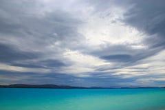 打旋在普卡基湖鲜绿色表面的黑暗的云彩  库存照片