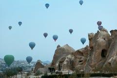 打来打去的 热空气在天空的气球飞行在与洞的岩石上 库存图片