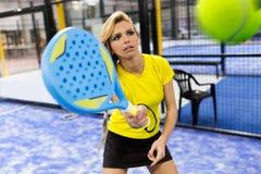 打桨网球的美丽的少妇室内 库存照片