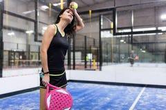打桨网球的美丽的少妇室内 免版税库存图片