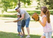 打棒球的家庭在公园 库存照片