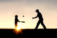 打棒球的父亲和儿子剪影外面 免版税库存图片
