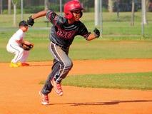 打棒球的男孩,跑根据 库存照片