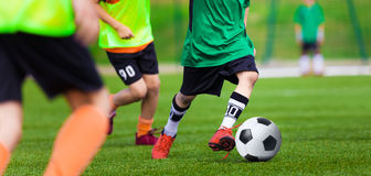 打橄榄球在运动场的孩子足球赛 男孩戏剧足球比赛 免版税库存照片