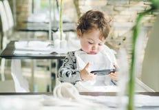 打比赛与智能手机的逗人喜爱的孩子 免版税库存图片