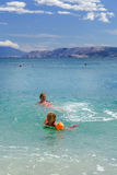 打比赛和游泳在海的两个姐妹 库存照片
