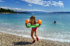 打比赛和游泳在海的两个姐妹 免版税库存图片