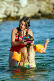 打比赛和游泳在海的两个姐妹 免版税库存照片