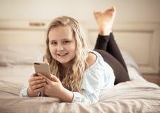 打比赛和观看在社会媒介的愉快的逗人喜爱的孩子录影在手机 免版税库存照片