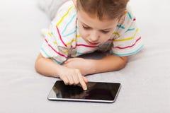 打比赛或浏览片剂的co的微笑的儿童男孩互联网 免版税库存照片