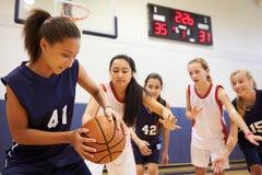 打比赛的女性高中蓝球队 库存照片