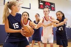 打比赛的女性高中蓝球队 免版税库存照片
