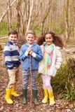 打比赛的小组孩子在森林里 库存图片