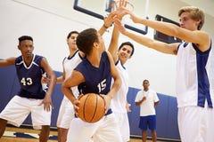打比赛的男性高中蓝球队 免版税库存图片