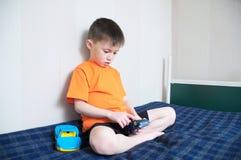 打汽车比赛,男孩使用与玩具坐床室内,孩子的男孩拿着两辆玩具汽车单独 图库摄影