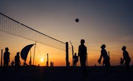打沙滩排球的人Silhouets在晚上荣耀时间 免版税库存图片