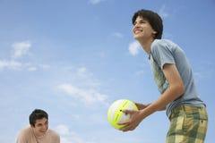 打沙滩排球的十几岁的男孩 免版税库存照片