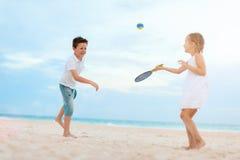 打海滩网球的孩子 免版税库存图片