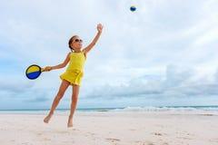 打海滩网球的小女孩 免版税库存图片