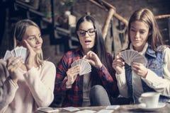 打游戏卡的咖啡馆的三个女孩 库存照片