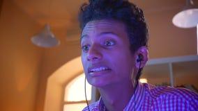 打电子游戏以兴奋的年轻可爱的印度男性博客作者特写镜头射击户内在一栋舒适公寓 股票录像