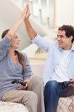 打电子游戏的一对快乐的夫妇的纵向 免版税库存照片
