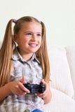 打电子游戏的女孩。 免版税库存照片