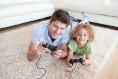 打电子游戏的微笑的男孩和他的父亲 免版税库存图片