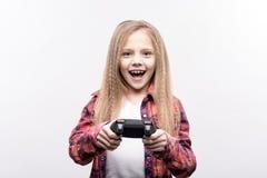 打电子游戏的欢乐的小女孩 库存照片