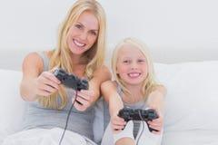 打电子游戏的母亲和女儿 免版税库存照片