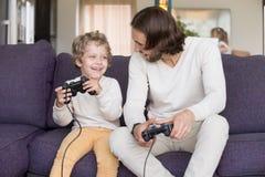 打电子游戏的父亲和儿子坐长沙发 免版税库存照片