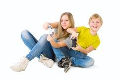 打电子游戏的男孩和女孩 免版税库存图片