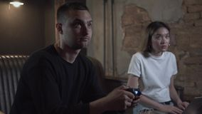 打电子游戏的画象年轻人坐沙发在有键入在a的逗人喜爱的smilling的女孩的顶楼样式屋子 影视素材