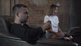 打电子游戏的画象年轻愉快的人坐沙发在顶楼样式屋子 让烦恼的女朋友 影视素材