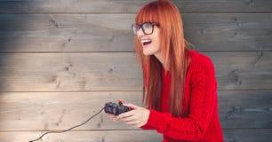 打电子游戏的红头发人妇女对木墙壁 免版税库存照片